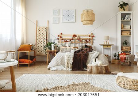 Spacious bright cozy bedroom with fresh plants and wooden decorations