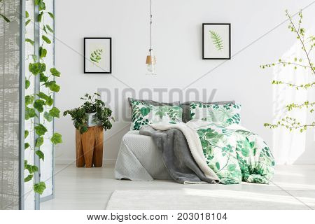 Plant on wooden designer table next to king-size bed with floral bedding in green bedroom with handmade lamp