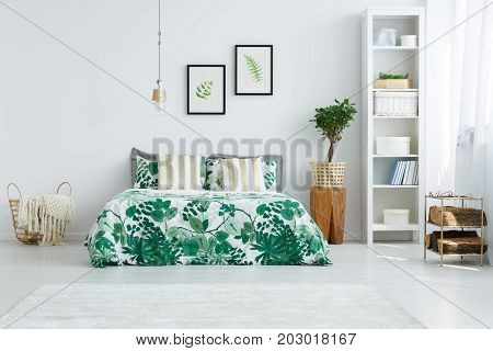 Striped gold pillows on bed with green quilt in cozy bedroom with small tree on wooden stool and knit blanket in basket