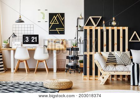 Big scandi desk designer chairs computer poster and rack in modern cozy room for a teenager with black and white interior design and wooden pallet decor in living area with sofa