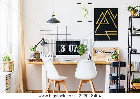 Black and golden geometric poster hanging above white and wooden desk space in scandinavian style with designer chairs monstera plant and industrial accessories like lamps cart and metal rack