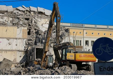 MAGDEBURG, GERMANY - November 8, 2016: Excavator in action. The Blue Bock, a landmark of the city, is demolished.