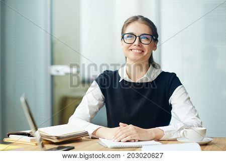 Young smiling businesswoman in eyeglasses sitting by her workplace