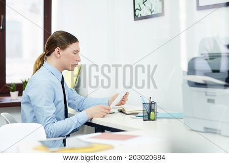 Young economist reading paper or contract by his workplace