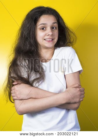 The teenage girl freezing. Yellow background. Portrait.