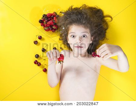 Funny Boy With Wide Open Eyes And Fresh Berries In His Hands, Happy Boy With A Surprised Look.yellow