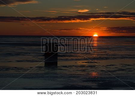 Sunset over an ice fishing shed on a frozen harbor in rural Prince Edward Island, Canada.