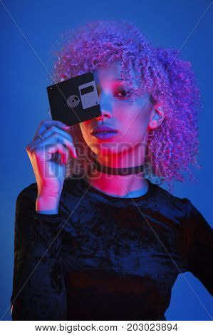 flashback of a millennial woman holding an obsolete diskette from the nineteens