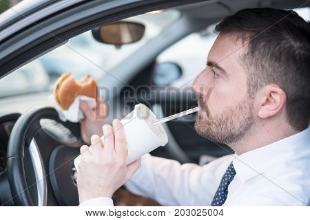 Man Eating An Hamburger And Driving Seated In Car