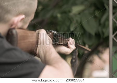 Man charging double barreled hunting rifle closeup