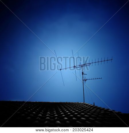 Silhouette of TV antenna installed on roof with dark blue sky background; wires for receiving transmitted analogue signal to home television - Copy space on top and left sides