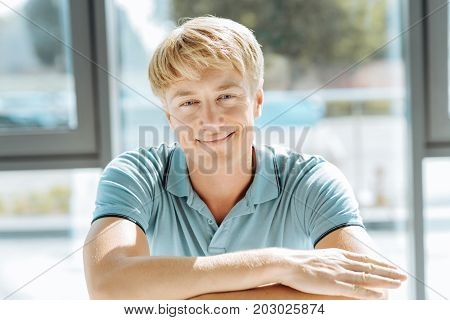 Say cheese. Delighetd young blonde man smiling and folding his hands while posing in front of the camera
