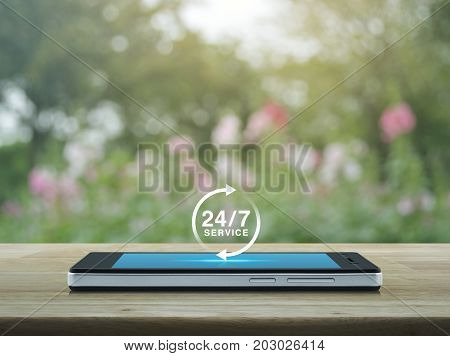 24 hours service icon on modern smart phone screen on wooden table over blur pink flower and tree Full time service concept