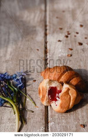 Delicious breakfast on wooden background. Sweet croissant with fruit jam and granola with spring blue snowdrops nearby. Morning fresh and tasty meal. Food photography close up
