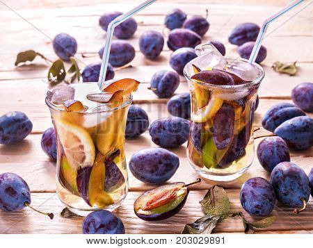 Refreshing drink from fresh juicy sweet plums with lemon in glass mugs with ice cubes on a wooden background with plums and green leaves