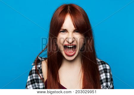 Angry screaming woman on pop blue backdrop. Rage emotion background. Evil young female shouting, furious feelings, conflict person