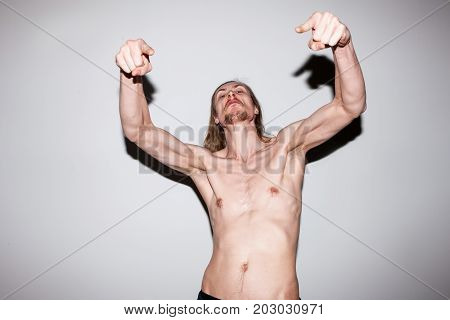 Aggressive strong man. Male showing off muscles. Naked scary guy frightening someone, aggression concept
