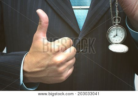 Business man showing thumbs up gesture by one hand and holding pocket watch by another hand. Time is money concept. Start to a busy day concept. Done on time concept.
