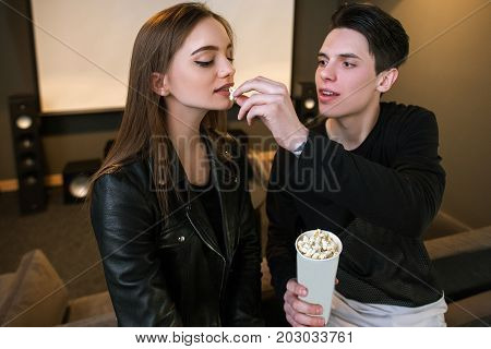 Young couple on date. Seductive background. People in home cinema with junk food, atmospheric comfort place