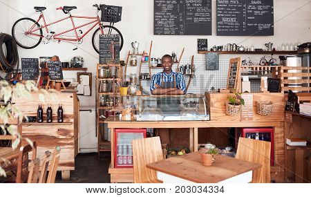 Portrait of a handsome young African man smiling and standing with his arms crossed behind the order counter of his trendy cafe