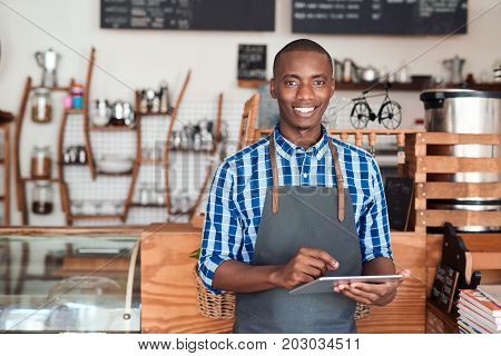 Portrait of a smiling young African entrepreneur in an apron leaning against the counter of his trendy cafe using a digital tablet