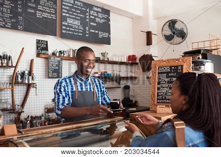 Smiling young African barista standing at the counter of a trendy cafe handing a fresh cappuccino to a female customer