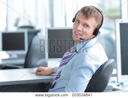 Happy young business man in headphone looking at camera
