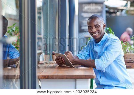 Portrait of a young African man smiling while sitting outside at a counter of a sidewalk cafe working online with a digital tablet