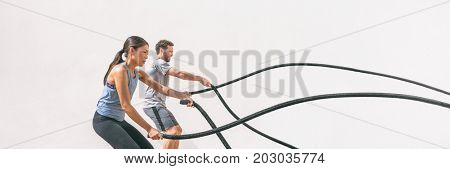 Gym fitness sport fit couple working out battle rope exercise banner panorama. Woman and man cross training arms muscles and cardio with battling rope. Core workout panoramic crop.