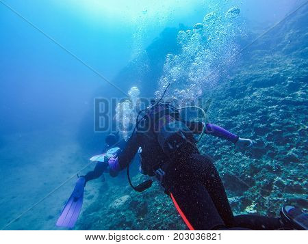 Scuba Divers Exploring The Underwater Landscape.  Scuba Divers And Air Bubbles Against The Sunlight.