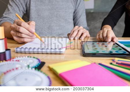 Two young dressmaker or designer colleagues working as fashion designers and drawing sketches for clothes choose color bar in tablet profession and job occupation Fashion Designer Stylish Concept.