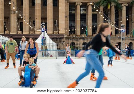 Brisbane, Australia - July 9, 2017: families ice skating on King George Square in front of Brisbane Town Hall during the Winter Festival.