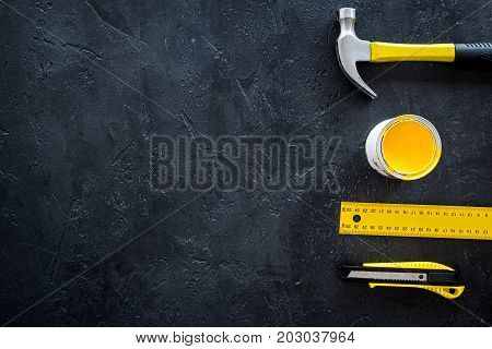 constructor desk with set of building implements and paint on dark desk background top view mock up