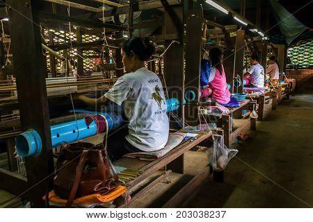 SIEM REAP CAMBODIA - AUGUST 24 2015: Women weave decorative cloths with silks at a silk farm.
