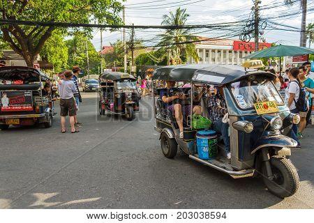CHIANG MAI THAILAND - 6/13/2015: Tourists ride tuk-tuks around the city.