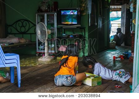 SIHANOUKVILLE CAMBODIA - 7/20/2015: Two girls sit on the floor and color inside their house in a rural fishing village.