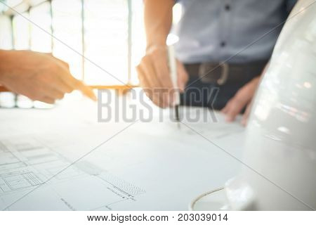 Image of engineer or architectural project Close up of hands architects engineering working on blueprint with engineering equipment tool blurred background.