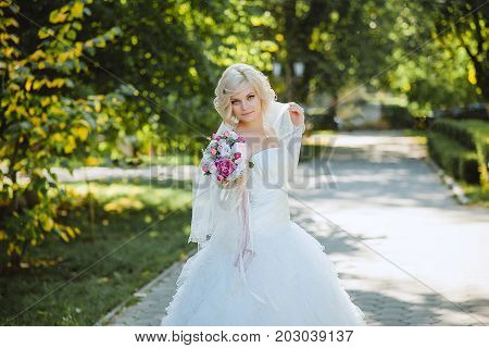 An innocent young bride boasts of her beauty in a city park.