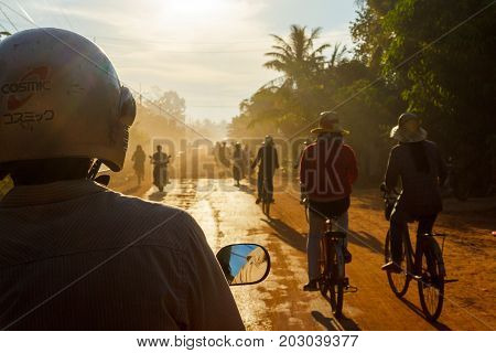 SIEM REAP CAMBODIA - SEPTEMBER 5 2015: Riding in a tuk-tuk while others bicycle and motorbike down a countryside dirt road.