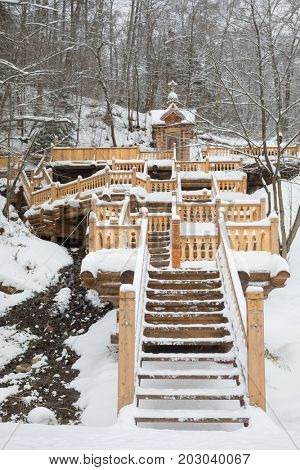 Wooden stairs with carving leading to fountain in Russian Orthodox Monastery at winter day