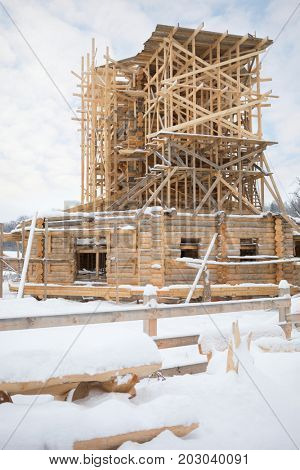 Wooden old-style building under construction and scaffolding in Russian Orthodox Monastery at winter day