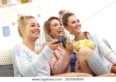 Three beautiful young women watching tv at home