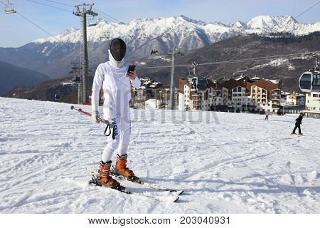Skier with phone stands at ski resort at winter day among mountains