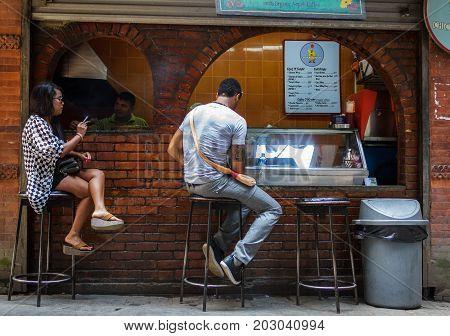 KATHMANDU NEPAL - 9/23/2015: Customers at a small streetside cafe in the Thamel district of Kathmandu Nepal.