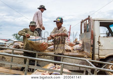 SIHANOUKVILLE CAMBODIA - 7/20/2015: Cambodian laborers offload bags of Ammonium Sulphate Fertilizer in a small fishing village.