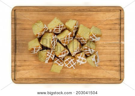 Top view glazed  mini pieces of lemon cake on wooden plate isolated over white background
