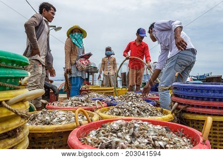SIHANOUKVILLE CAMBODIA - 7/20/2015: A group of workers help fishermen prepare on the docks of a fishing village.