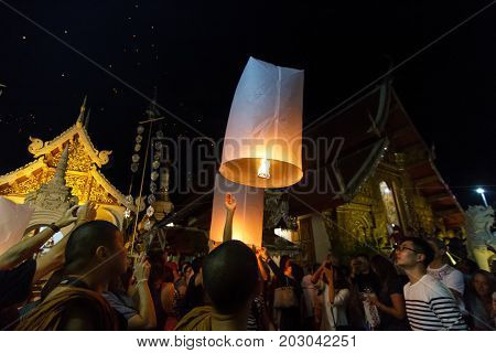 CHIANG MAI THAILAND - 12/30/2015: A group releases floating lanterns at a Buddhist temple on New Year's Eve in Chiang Mai Thailand.