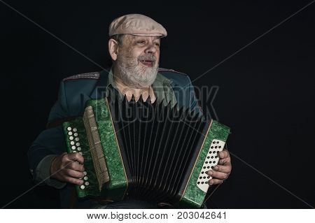 Nice portrait (low key) of an old retired military man singing while playing accordian
