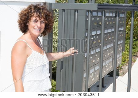 Woman Enters Her Residence By The Gate In Front Of The Mailboxes